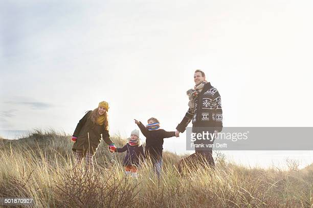 Mid adult couple standing in sand dunes with their son, daughter and dog