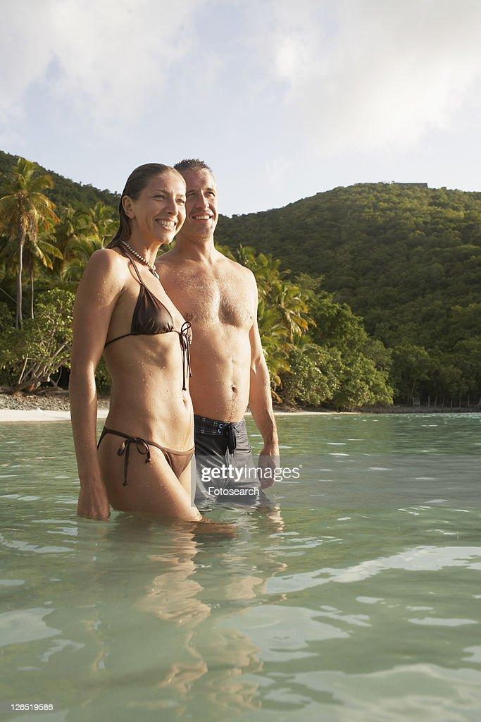 Mid adult couple standing in water near beach, St John, US Virgin Islands, USA