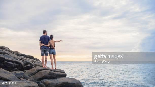 Mid adult couple standing on rocks on coastline, Sri Lanka