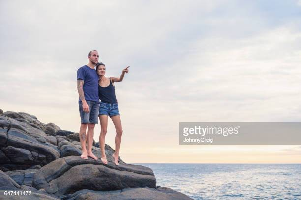 Mid adult couple standing on rocks, woman pointing into distance