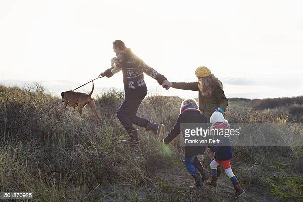 Mid adult couple strolling in sand dunes with their son, daughter and dog