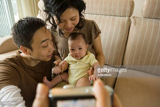 Mid adult couple taking a photograph with their daughter