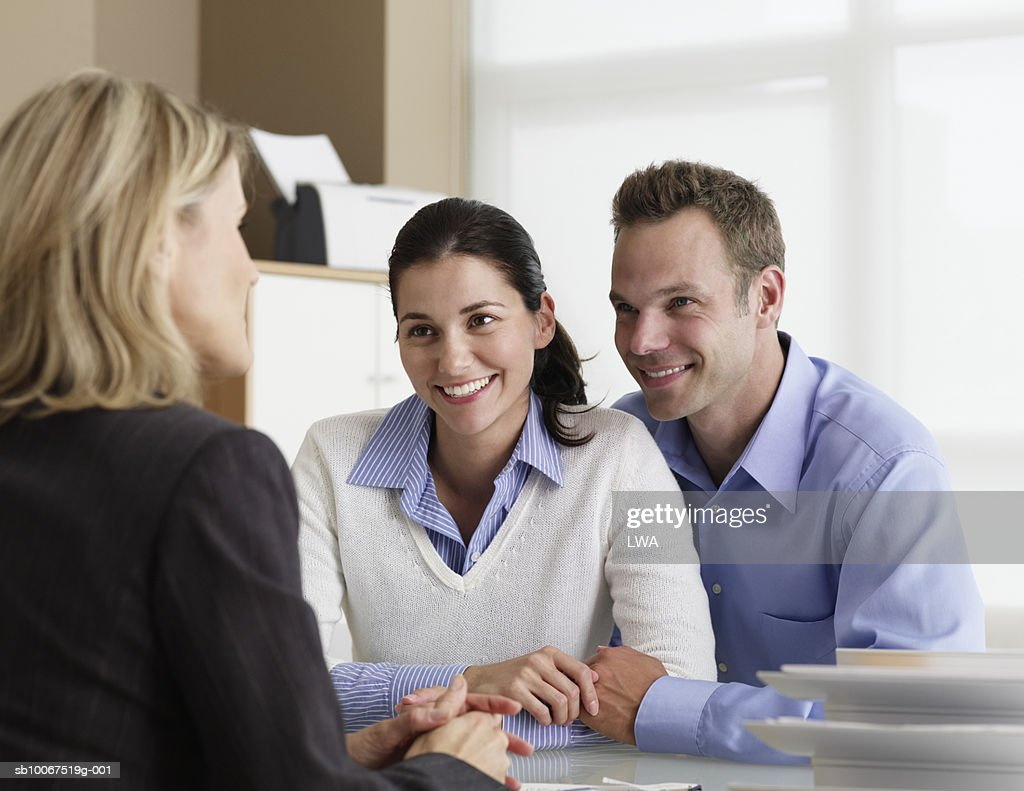 Mid adult couple talking with insurance agent in office, smiling : Stock Photo