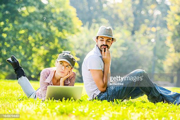 Mid Adult couple using laptop and digital tablet outdoors