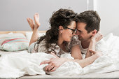 Mid adult couple wearing pyjamas lying on front on bed, face to face