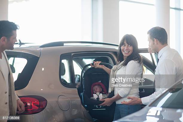 Mid adult couple with baby girl trying out baby seat in car dealership