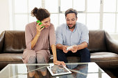 Mid adult couple with digital tablet, woman on cell phone