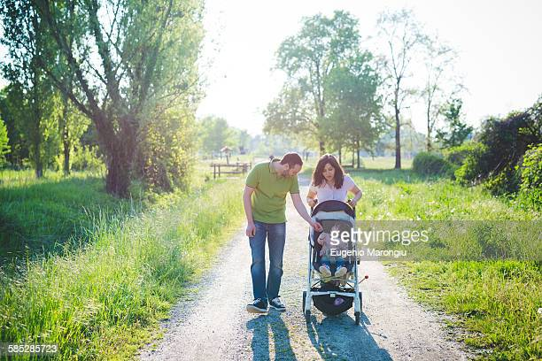 Mid adult couple with toddler daughter in pushchair strolling in park