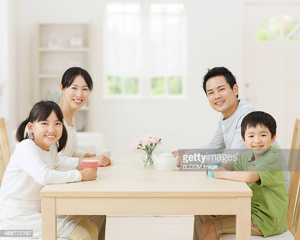 Mid Adult Couple With Two Children Drinking Tea