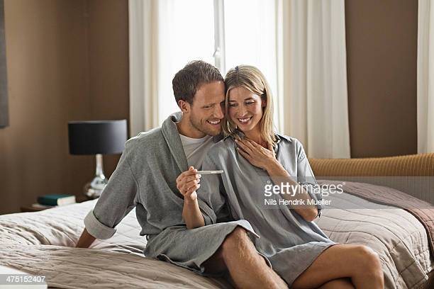 Mid adult couple, woman holding pregnancy test