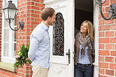 Mid adult couple, woman opening front door