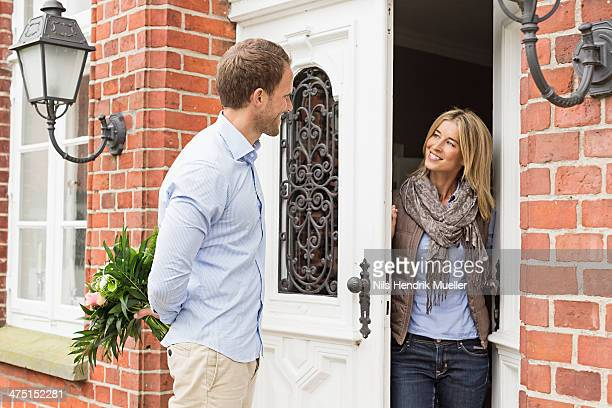 Mid adult couple, woman opening front door