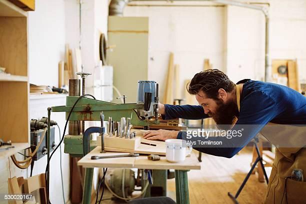 Mid adult craftsman using machine in pipe organ workshop