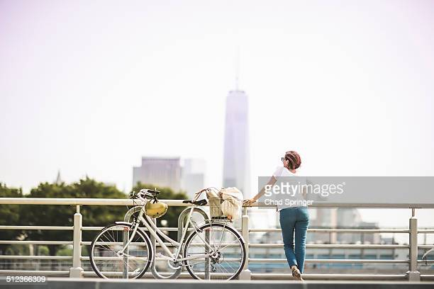 Mid adult female cyclist gazing at city from riverside, New York City, USA