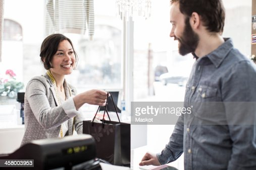 Mid adult female design professional giving shopping bag to customer at cash counter in studio