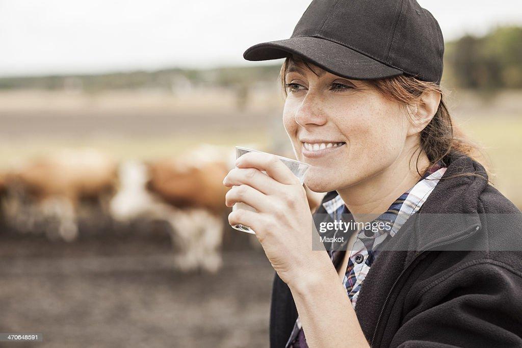 Mid adult female farmer drinking milk in farm