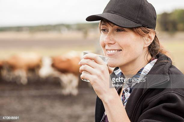 Mid adult female farmer drinking milk in farm