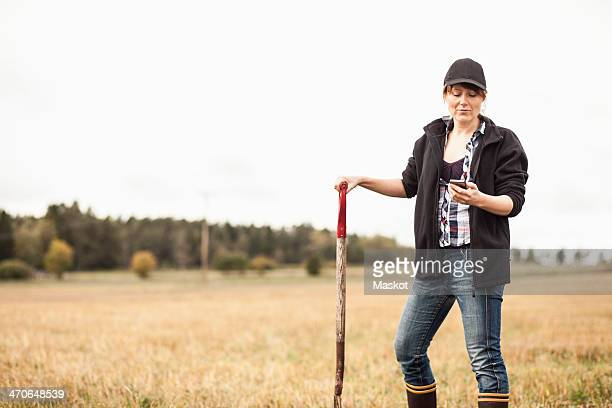Mid adult female farmer using mobile phone in field