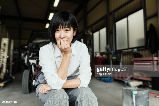 Mid adult female mechanic working in an automotive repair shop