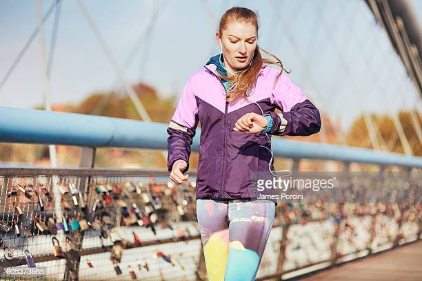 Mid adult female runner checking time whilst running across bridge