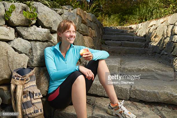 Mid adult female runner taking a break in park eating an apple