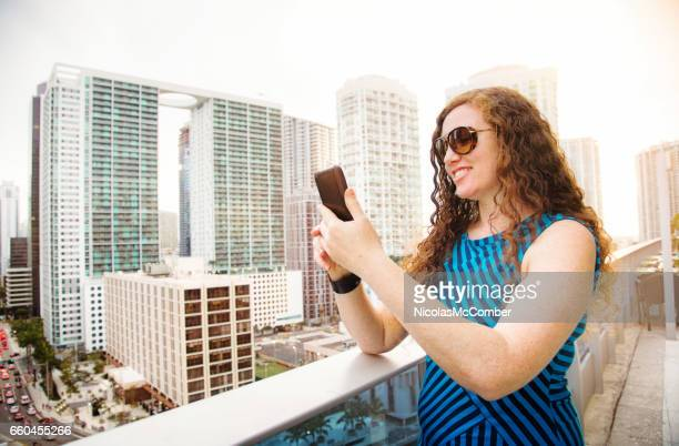 Mid adult female social networking with mobile phone in Miami Florida