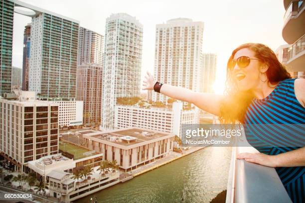 Mid adult female waving to the city on balcony in Miami Florida