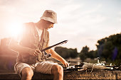 Mid adult fisherman preparing his fishing rod at sunset.