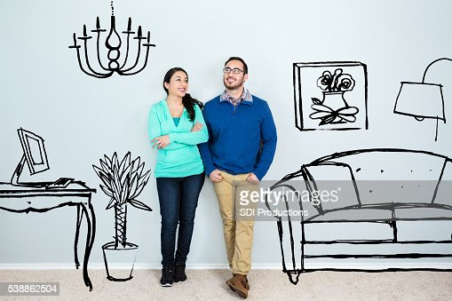 Mid adult Hispanic couple daydream in their new home