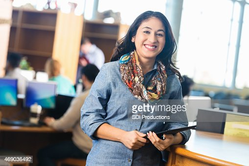 Mid adult Hispanic student holding digital tablet in college library
