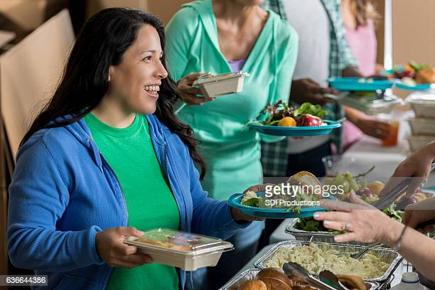 Mid adult Hispanic woman receives meal in soup kitchen