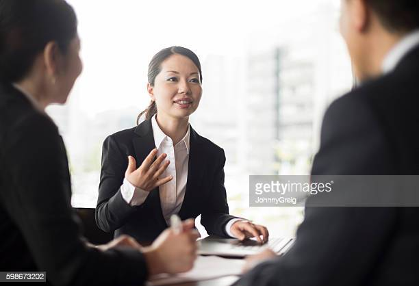 Mid adult Japanese businesswoman in meeting with colleagues, gesturing
