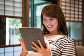 Mid adult Japanese woman using tablet, smiling