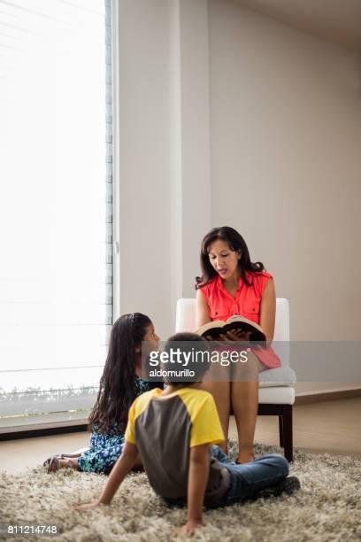 Mid femme latine adulte lecture à ses enfants