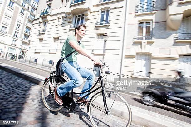 Mid adult male cyclist speeding down cobbled street, Paris, France