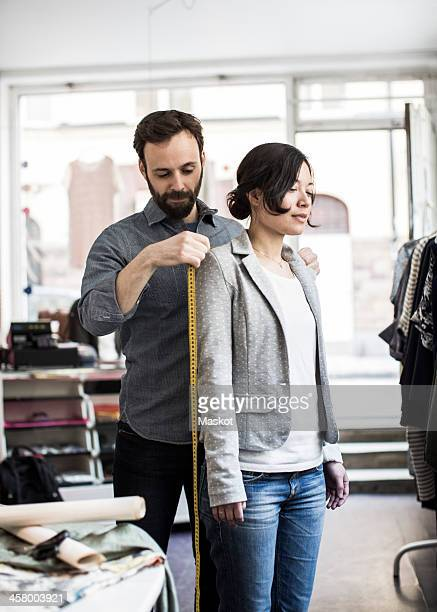 Mid adult male fashion designer measuring woman's shoulder at studio
