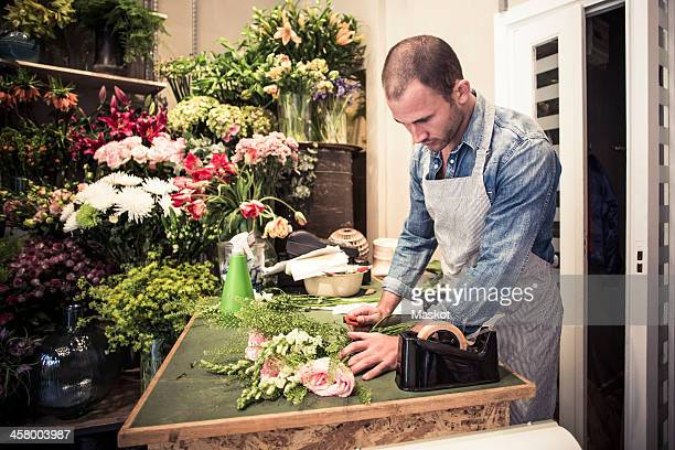 Mid adult male florist preparing bouquet of flowers at desk in shop