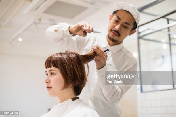 Mid adult male hair salon owner cutting young female's hair.