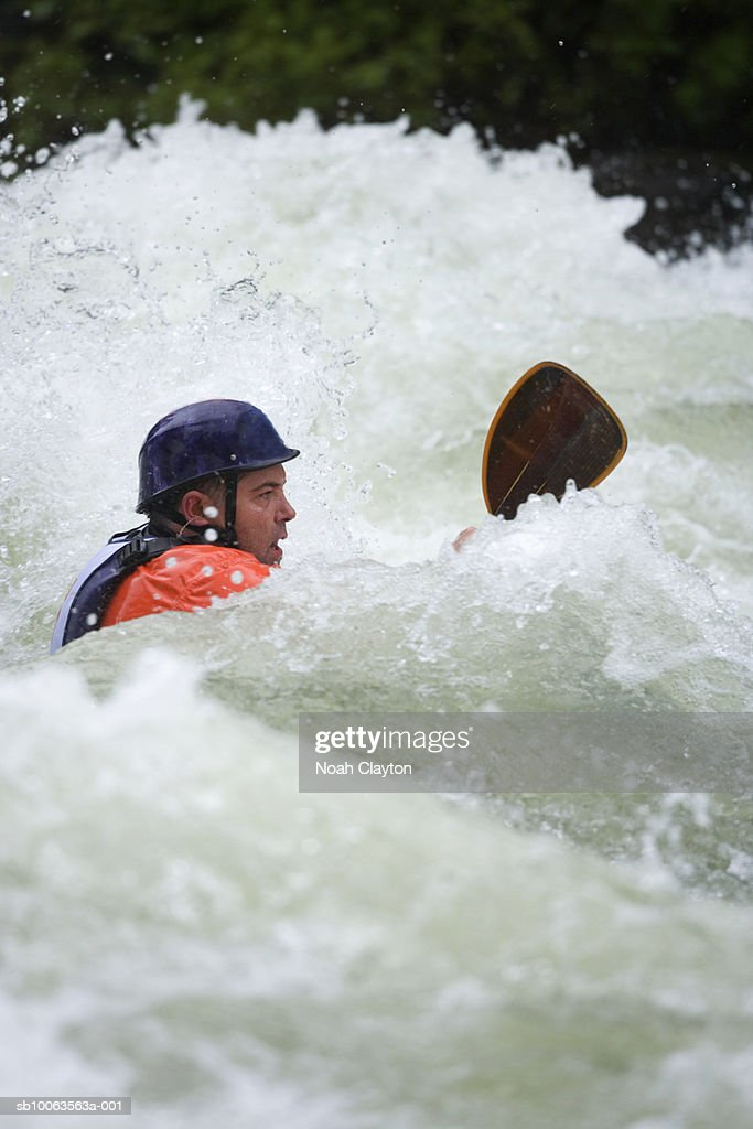 Mid adult male kayaker paddling through big waves