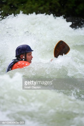 Mid adult male kayaker paddling through big waves