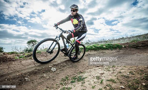 Mid adult male mountain biker speeding on track corner, Cagliari, Sardinia, Italy
