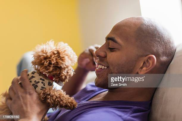 Mid adult male relaxing on sofa with dog