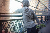 Mid adult male runner stretching legs on bridge