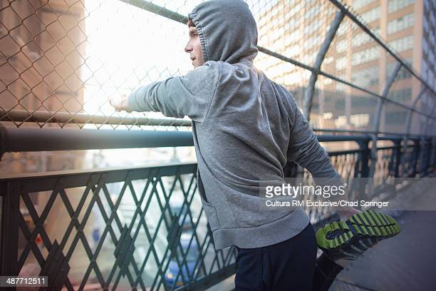 Mid adult male runner stretching legs on bridge