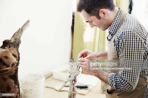 Mid adult male sculptor working on table lamp in studio
