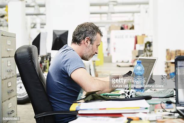 Mid adult male sitting at desk, using laptop