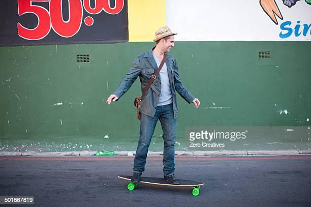 Mid adult male skateboarding on city street