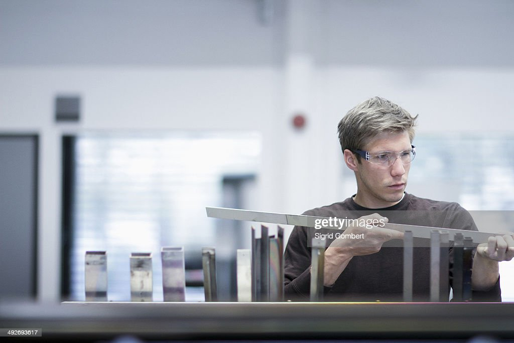 Mid adult male technician checking quality of products in engineering plant : Stock Photo