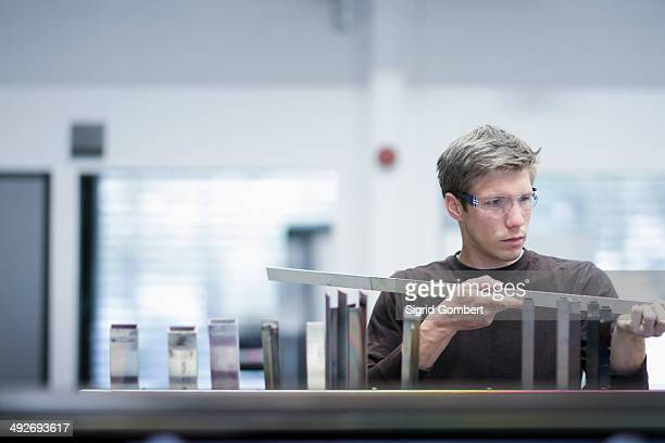 Mid adult male technician checking quality of products in engineering plant