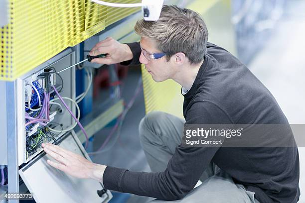 Mid adult male technician maintaining equipment in engineering plant